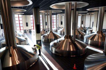 A worker inspecting vats at an Anheuser-Busch InBev brewery in Leuven, Belgium.
